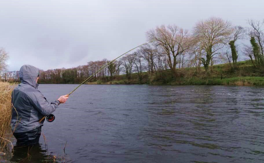 Un pêcheur joue un saumon sur la rivière Feale